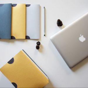 Laptop und verschiedene bunte Ordner