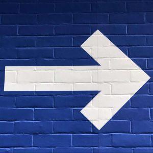 Weiterleitung: weißer Pfeil auf blauer Wand